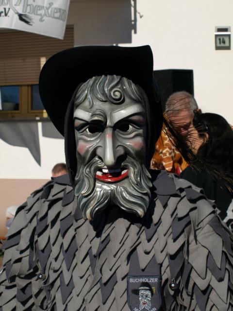 Graue Maske mit Vollbart und schwarzem Hut. Das Häs ist grau mit dunkelgrau abgesetzten Flecken ...